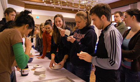 Students in a Jan Term Italian cooking class unmold panna cotta from ramekins.