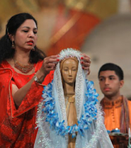 A woman adorns a statue of Mary during a pilgrimage to the Basilica of the National Shrine of the Immaculate Conception in Washington in this 2010 file photo. (CNS photo/Nancy Wiechec)