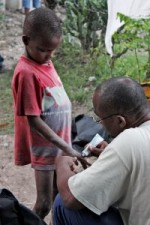 Professor Claude Malary, during SMC trip to Haiti, applies first aid ointment to a child's hand.